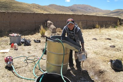 Dario processing archaeological sediments by flotation in the village of Totorani.