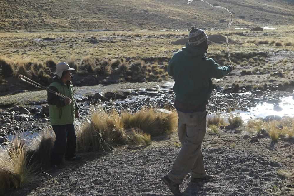 Mateo teaches Nathaniel to use an honda--Andean sling--at the Ccoypani field site.